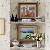Bilder, blau-weisses Porzellan und Silberkanne mit weißen Rosen auf Regalen in einer Wandnische