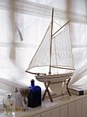 Modellboot auf Fensterbank und weißer Vorhang