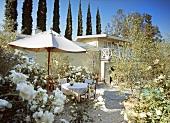 Mediterraner Garten mit Terrassenplatz vor Landhaus