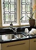 Arbeitsplatte aus schwarzem Granit mit Edelstahlspüle und Zimmerpflanze vor Bleiglasfenster