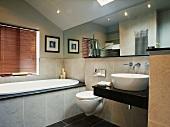 Modern gefliestes Badezimmer mit grossem Wandspiegel