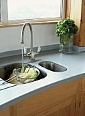 Graue Arbeitsplatte mit Spüle und Küchenarmatur und Gemüse im Sieb