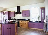 Violette Einbauschränke und braunmelierter Fliesenboden in moderner Küche