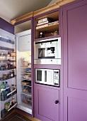 Violetter Einbauschrank mit Kühl-Gefrierkombination und offener Tür neben Einbaugeräten