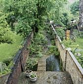 Schmaler Stadtgarten mit Steinmauern und Steg über Teich