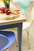 Rote Paprika und Möhren auf Schneidebrett auf modernem Holztisch und Stühle im Bauhausstil