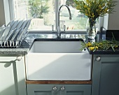 Einbauwaschbecken mit Granit Arbeitsplatte und Vase mit gelben Mimosen vor Fenster