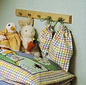 Nahaufnahme eines Kinderkissens mit kariertem Überzug mit Bildmotiv, Stofftieren, einer Kinder-Garderobe und daran hängenden kleinen Säckchen im gleichen Karo