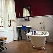Traditionelles schwarz-weiss Badezimmer, mit einer freistehenden Badewanne mit einem Terracotta-Fliesenboden und halb hoch weiss gefliesten Wänden