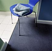 Badezimmerdetail: Handtücher auf blauem Stuhl