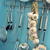 Nahaufnahme eines Stahlgestells mit daran hängendem Knoblauchzopf und Edelstahl-Küchenutensilien