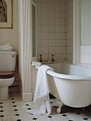 Traditionelles Badezimmer mit Keramikfliesen, Clawfoot- Badewanne und daran hängendem weissen Handtuch