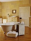 Badezimmer mit freistehender Clawfoot-Badewanne, einem Lloyd Loom Tisch mit Glasplatte, einem cremefarbenen Handtuchstapel und mit aufgemaltem Steinwand-Effekt an den Wänden