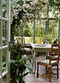 Offene Tür zu einem Wintergarten mit antiken, hölzernen Stühlen und weißem Tisch; darüber eine weissblühende Pflanze