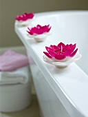 Lotus flower-shaped candles on the edge of a bathtub