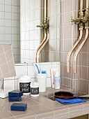 A tiled bathroom with taps and bathing utensils in front of a mirror