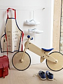 A wooden training bike, an apron and shoes in a child's bedroom