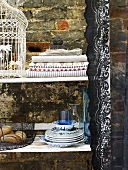 Plates, a bread basket, tablecloths and a bird cage on a shelf against a brick wall
