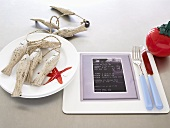 A place setting with a menu and maritime decorations
