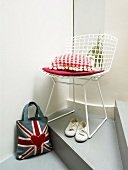A Union flag bag, a cushion on a chair and a pair of shoes underneath