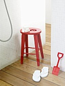 A red stool, a spade and white flip-flops in a shower