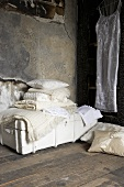 Cream-coloured blankets and cushions on a chest in an attic