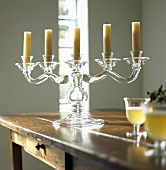 A five arm glass candle stick on a wooden table
