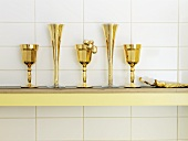 Golden wine glasses and champagne flutes on a shelf on a tiled wall