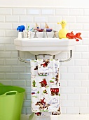 A wash basin with a child's towel and toys