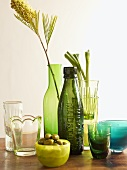 Green bottles, a vase, glasses and bowls with green olives