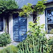 Weisses Landhäuschen mit blauer Doppeltür und Fensterrahmen