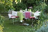 Tisch mit Decken und Stühlen mit Kissen auf dem Rasen im Garten am frühen Abend