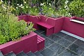 Terrasse mit grauen Fliesen, die pinkfarbenen Wände dienen als Abgrenzung von den Blumenbeeten