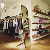 Bekleidungsgeschäft mit Standspiegel und Holzregalen