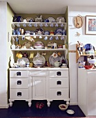 Regale mit Geschirr über weisser Kommode in einer Wandnische einer Küche