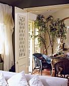 Blick auf ein Esszimmer mit runder Tisch und Korbsessel