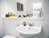 A wash basin and a mirror against a white tiled wall