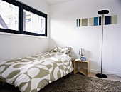 A modern bedroom with a transom window and a single bed with patterned bedclothes