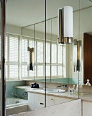 A bathroom with lights on a mirrored door