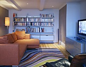 An open-plan living room with an orange corner sofa in front of a bookshelf and a rug with curved stripes