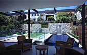 Retro-style armchairs in a living room in a newly built house with a view through a glass facade to an outdoor pool