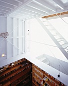A gallery with a white staircase and a view into an open study