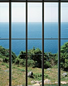 A view through a window to the garden and the sea