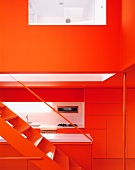 N open stairway with a view of a modern, red kitchen