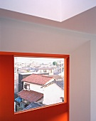 A room with a red wall and a window