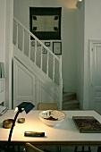 Kleiner Raum mit brennender Lampe am Tisch und Treppe im Hintergrund