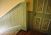 Treppenhaus mit grüner Holzverkleidung als Treppengeländer