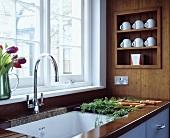 Holzarbeitsplatte mit Designer Küchenarmatur und Tassen auf Holzablage