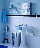 Standwaschbecken vor weissen Wandfliesen und Spiegelschrank vor blauer Wand