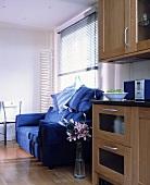 Blaues Polstersofa vor Fenster neben Küchenschrank